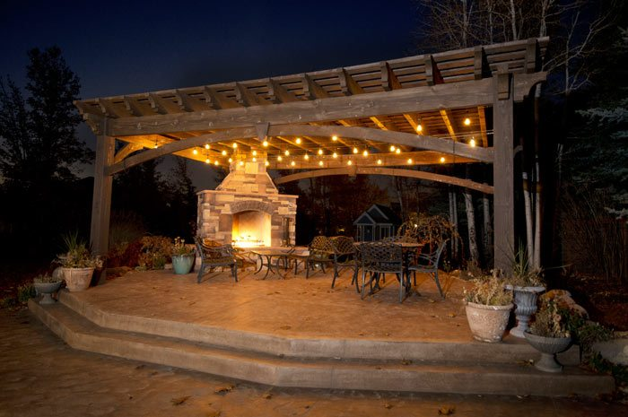 night time solid wood pergola with outdoor fireplace lights