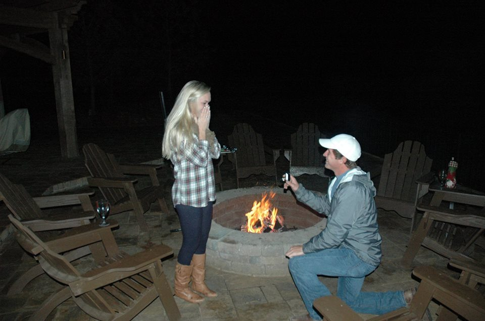 Couple marriage proposal by a fire pit