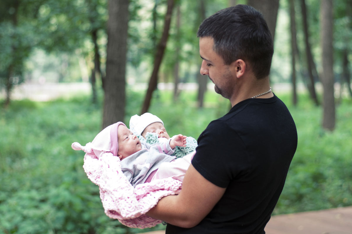 dad holding twin babies